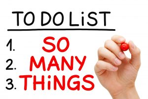 Hand writing So Many Things in To Do List with red marker isolated on white.